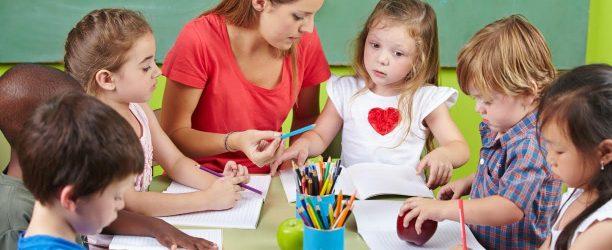 Kinder lernen gemeinsam schreiben in Vorschule mit der Erzieherin